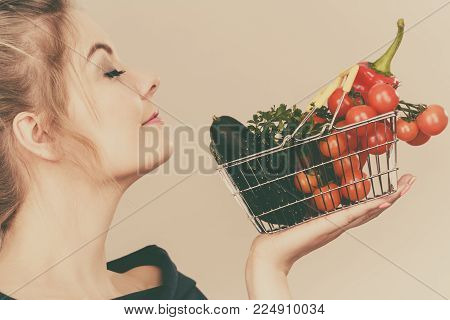 Buying good food, vegetarian products. Attractive woman holding shopping basket with green red vegetables inside, smelling with eyes closed, recommending healthy high fibre diet, on grey