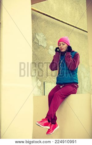 Outdoor sport exercises, sporty outfit ideas. Woman wearing warm sportswear relaxing after exercising outside during cold weather.