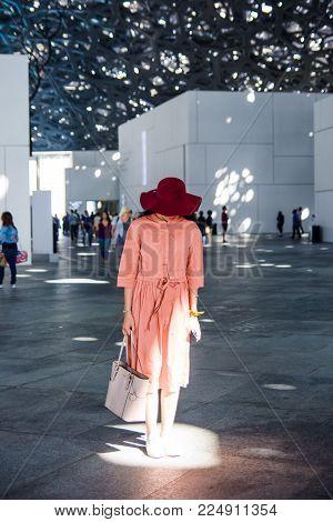 ABU DHABI, UNITED ARAB EMIRATES - JANUARY 26, 2018: Female tourist visiting Louvre museum in Abu Dhabi. Louvre is a new museum in United Arab Emirates opened on November 8th 2017