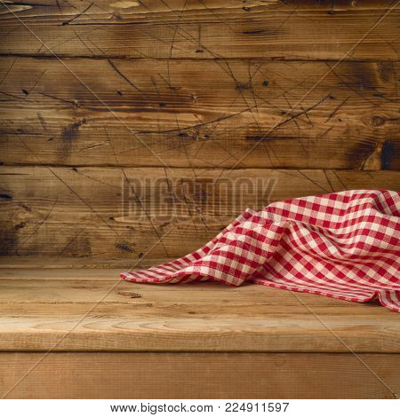 Empty wooden table with red checked tablecloth. Kitchen rustic background
