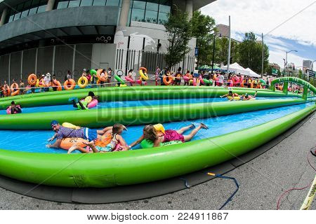 ATLANTA, GA - JULY 2017:  Hundreds of people with innertubes enjoy participating in a giant downhill waterslide at the Slide The City event in Atlanta, GA on July 15, 2017.