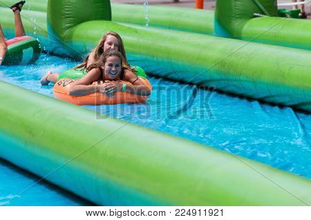 ATLANTA, GA - JULY 2017:  Teenage girls laugh as they travel down a giant slip-and-slide in an innertube, at the Slide The City event in Atlanta, GA on July 15, 2017.