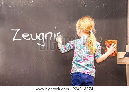 Cute little girl writing Zeugnis on chalkboard in a classroom - Translation Testimony