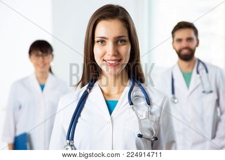 Portrait of a young female doctor in a clinic with colleagues on the background