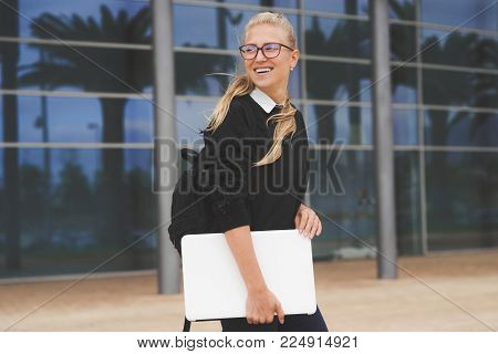 Young woman walking by the office building holding a laptop. Picture was taken in Gran Canaria, Spain