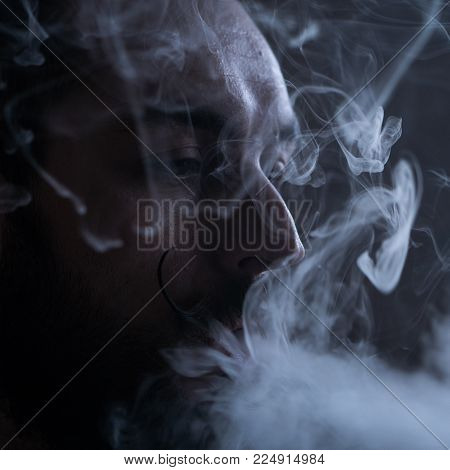 Young Man with Beard and Mustages Vaping an Electronic Cigarette. Vaper Hipster Smoke Vaporizer and Exhals Smoke Flow.