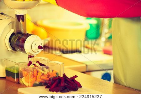 Woman hands adding different vegetables red and green in juicer maker. Housewife in kitchen making raw juice, preparing nutritious vitamin packed drink. Healthy eating, vegetarian food, dieting concept
