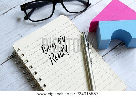 Sunglasses,home model,pen and notebook written 'BUY OR RENT?' on white wooden background.