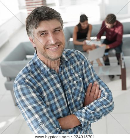 Smiling mature businessman in plaid shirt foreground