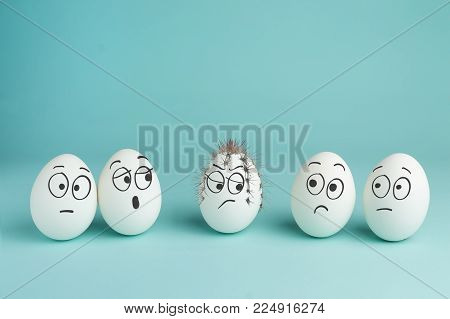 Bad character concept. Prickly egg. Five white eggs with drawn faces on a blue background.