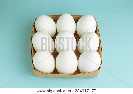 Chicken eggs in a wooden package. Nine white eggs in a square box on a blue background