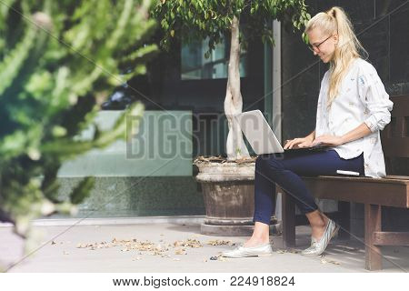 Young business woman working on here laptop sitting on a bench by the office building