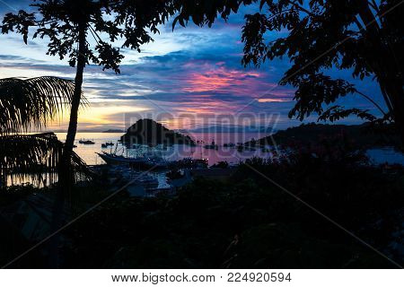Sunset at the harbour of Labuan Bajo with boats and hill and palm trees in the front, Flores, Inonesia