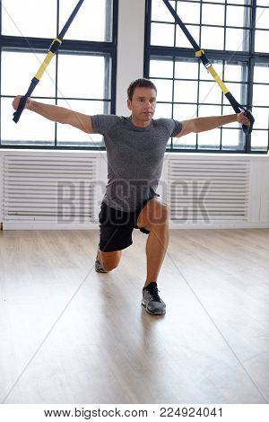 Middle age man doing exercises with expander in a gym club.