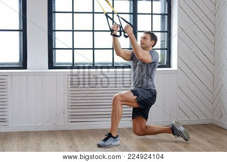 Sporty middle age man exercising with expander in a gym club.