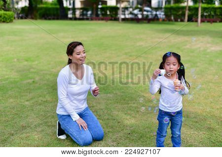 Family Concept. Happy male and female playing with children outside. Family is doing happy activities at Playground.  Parents are playing happily.