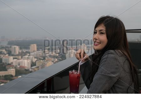 Concept of business celebrations. Asian businesswoman is drinking alcohol in the party. Young businesswoman celebrates the success of her work. Young businesswoman drinking in a business bar.
