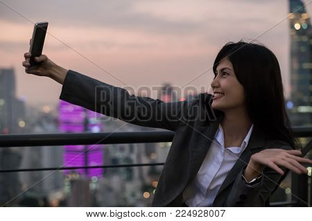 Business Concept. Asian businesswoman looking at mobile phone. Asian businesswoman happy at the top of the building. Beautiful young businesswoman Asians are happily playing mobile.