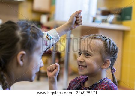 Two little girls fight with their fists