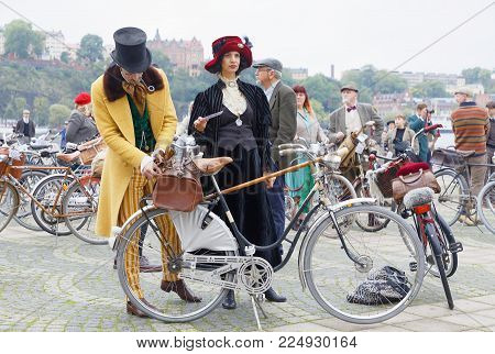 STOCKHOLM - SEPT 23, 2017: Elegant upper class lady and gentleman with bicycles dressed in yellow and black clothes, cylinder hat and feather hat from aprox 1900 in the Bike in Tweed event September 23, 2017 in Stockholm, Sweden