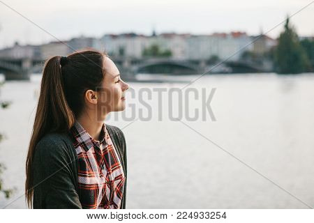 A young beautiful girl on the banks of the Vltava River in Prague in the Czech Republic, admires the beautiful view of the river and the architecture of the city and dreams.
