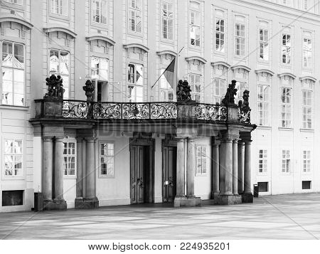 Entrance door with balcony to the Archives of Prague Castle on Third Courtyard, Prague, Czech Republic. Black and white image.