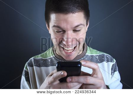 Portrait of a young man addicted to using smart phone or social media, modern social issue