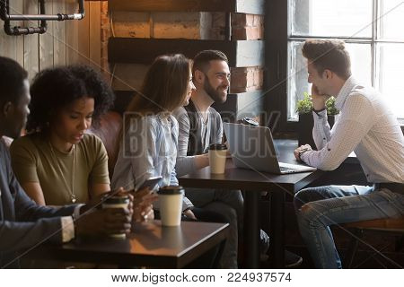 Diverse multiracial young people talking drinking coffee using devices in cozy coffeehouse, multi-ethnic african and caucasian millennials enjoy meeting sitting at coffeeshop tables together in cafe