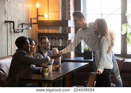 Happy couple get acquainted with multiracial people coming at meeting in cafe, young man introducing handshaking african guy from diverse friends group, new acquaintance and making first impression