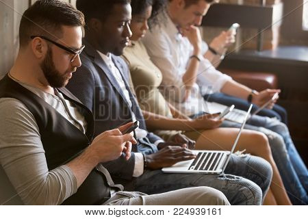Multi ethnic group of young people using electronic devices indoors, diverse african and caucasian millennial users holding smartphones and laptops sitting in row, obsessed gadget addicts concept