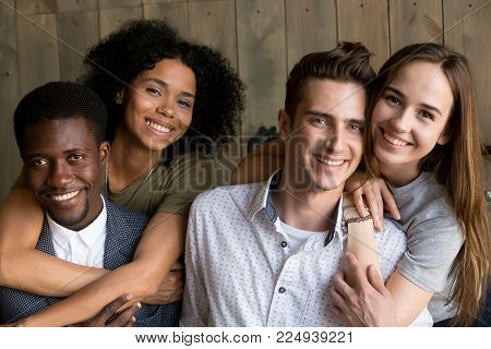 Portrait of two happy african american and caucasian couples embracing, young multiracial men and women in love hugging smiling looking at camera, diverse ethnicity and racial diversity concept