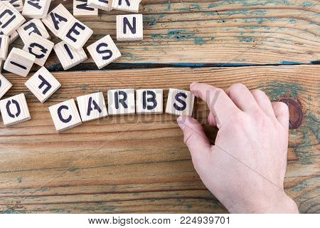 carbs. Wooden letters on the office desk, informative and communication background.