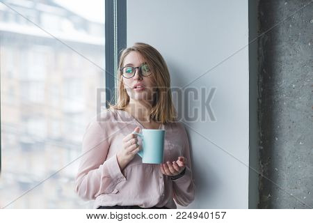The beautiful girl in the glasses stands in the wall near the window with a cup of coffee. The girl's office worker stands with a cup of drink in her hands and looks in the window.