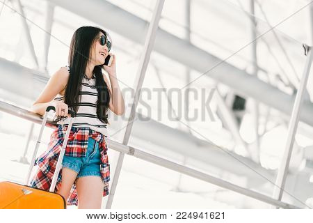 Cute young Asian traveler woman or college student using mobile phone call at airport terminal with luggage. Study or travel abroad, international tourism or telephone communication technology concept