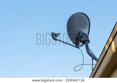 View looking up at a satellite dish on the roof of a generic building silhouetted against a blue sky, copy space, horizontal aspect