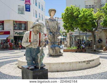 LAGOS, PORTUGAL - AUGUST 03, 2017: Live statue of a man giving a presentation on the street. Entertainment for the tourists.