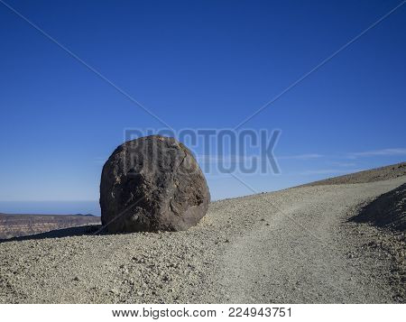 big accretionary lava ball - Huevo del Teide (Egg of Teide) in desert volcanic landscape with footpath on volcano pico del teide with clear blue sky background