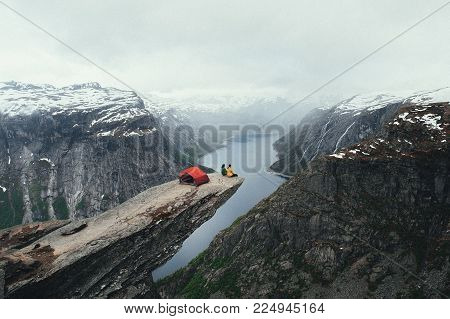 A man sits on the mountain's cliff edge of Trolltunga