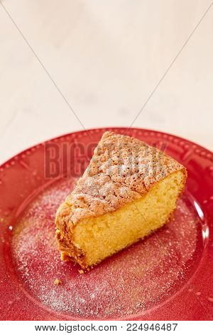 Homemade pie on a ceramic plate on a white wooden table. A piece of delicious carrot pie on a red shiny plate. Part of a homemade cupcake on a plate.