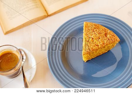 Homemade pie on a ceramic plate on a white wooden table. A piece of delicious carrot pie on a blue shiny plate and vintage old book. Part of a homemade cupcake on a plate with black coffee.