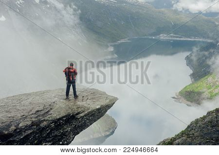 Amazing view of hiker man posing at troll tongue, at Norway mountains, freedom concept.Winter concept image of traveling man, happy, wild and free, lake.fjord.snow landscape, warm clothes, travel