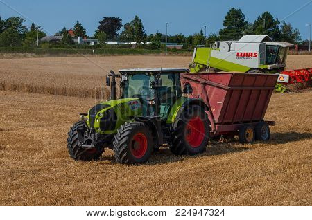 Vordingborg Denmark - August 14. 2015: Claas Tractor With A Grain Trailer And A Claas Harvester On A