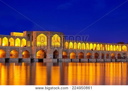 Isfahan, Iran - April 24, 2017: Night illumination of the arched stone Khaju bridge, crossing the Zayandeh river.