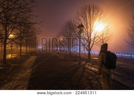 Fog in the city park at night by the light of street lamps during the thaw, street lamp close up and walking man with a backpack