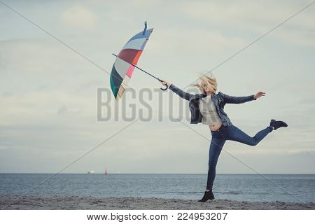 Happiness, enjoying cold autumn weather, feeling great concept. Woman jumping with colorful umbrella on beach near sea, sunny day and clear blue sky