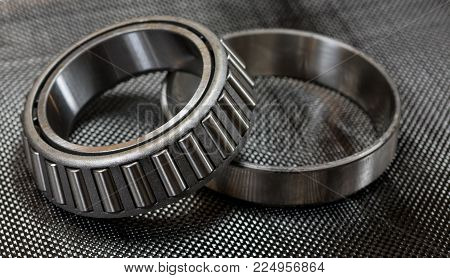 Antique automotive tapered roller bearing and race on plain weave carbon fiber cloth.