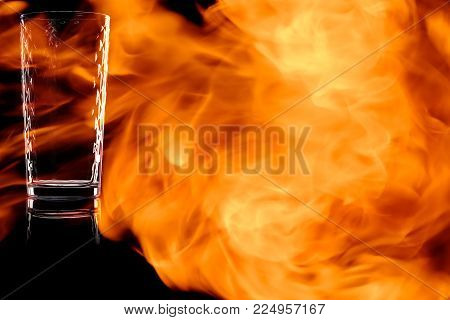 Faceted empty glass of water isolated on black background in the fire flames.