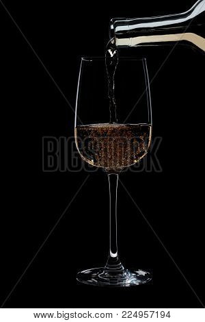 In a glass of poured white wine from a bottle isolated on a black background, the wine is Golden in color and bubbles.