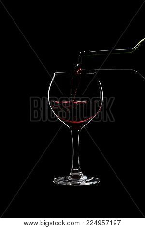 Glass of a red wine is pouring wine from a bottle of red . Filmed in close-up glass, where you pour the wine from the bottle.
