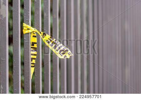 Crime scene border tape peace left on fence in UK.